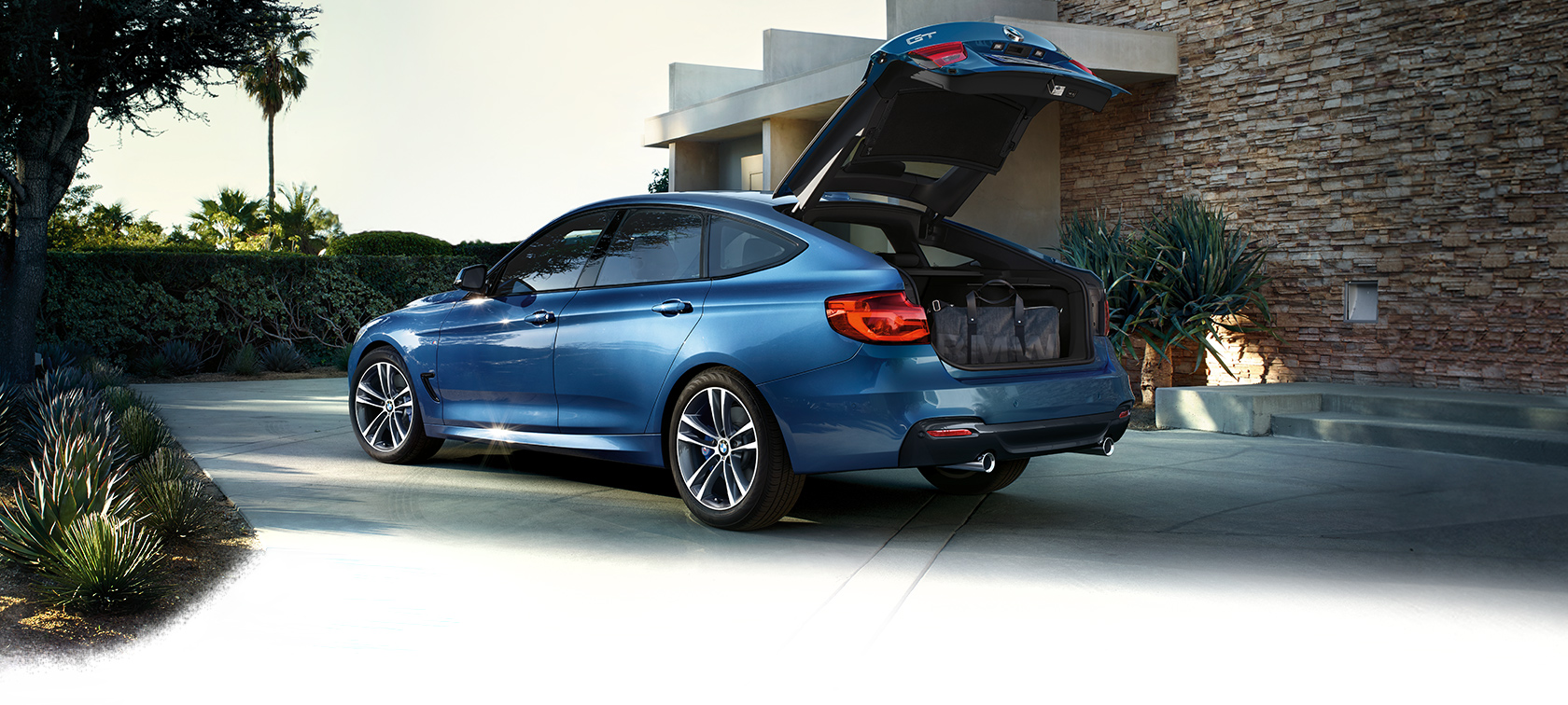 BMW 3 Series Gran Turismo: bright blue car with open trunk.