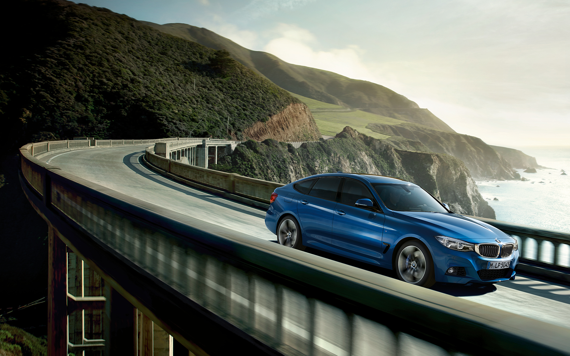 BMW 3 Series Gran Turismo: bright blue car fast driving on the highway bridge.