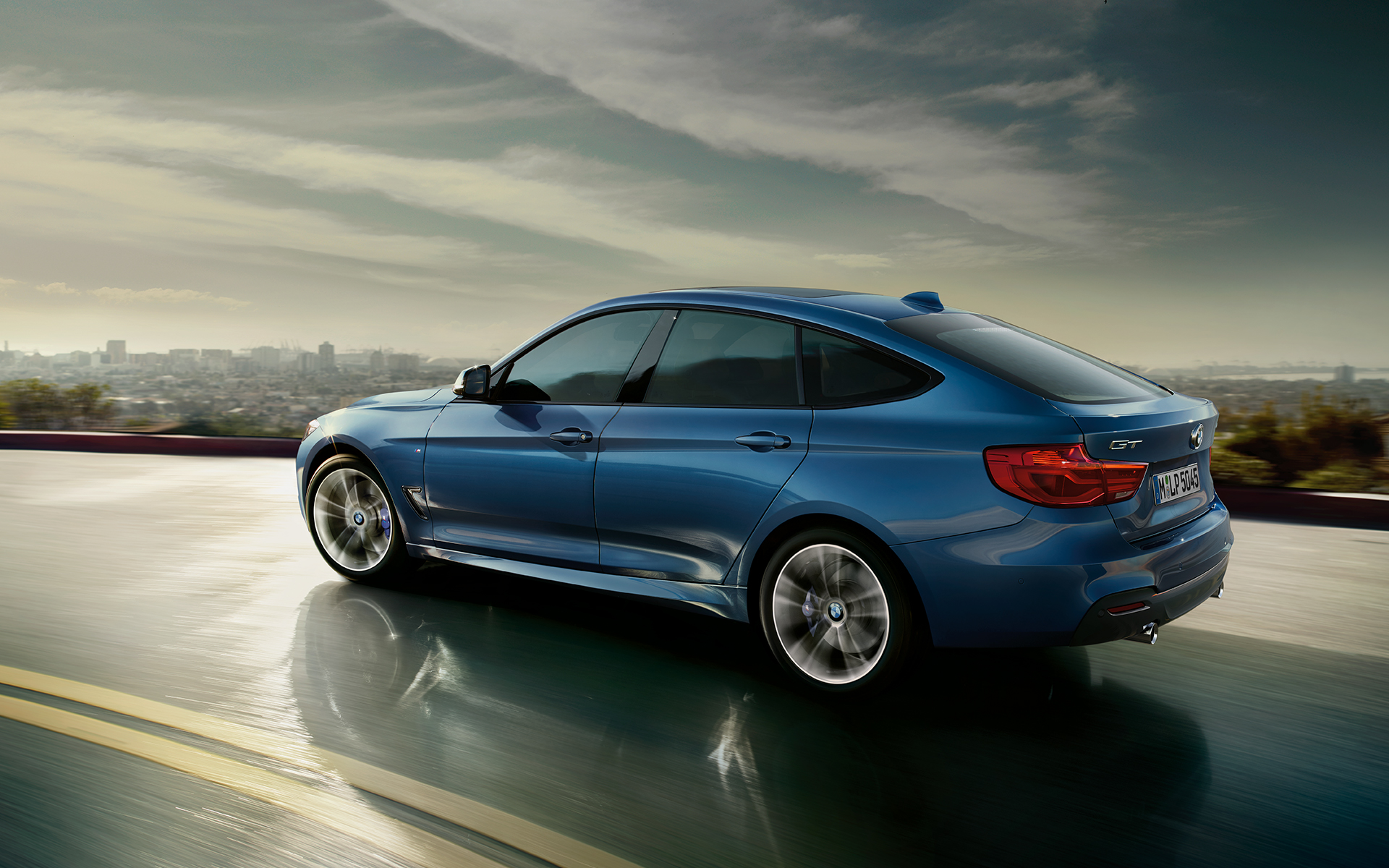 BMW 3 Series Gran Turismo: side view of car driving on highway with city scapes background.