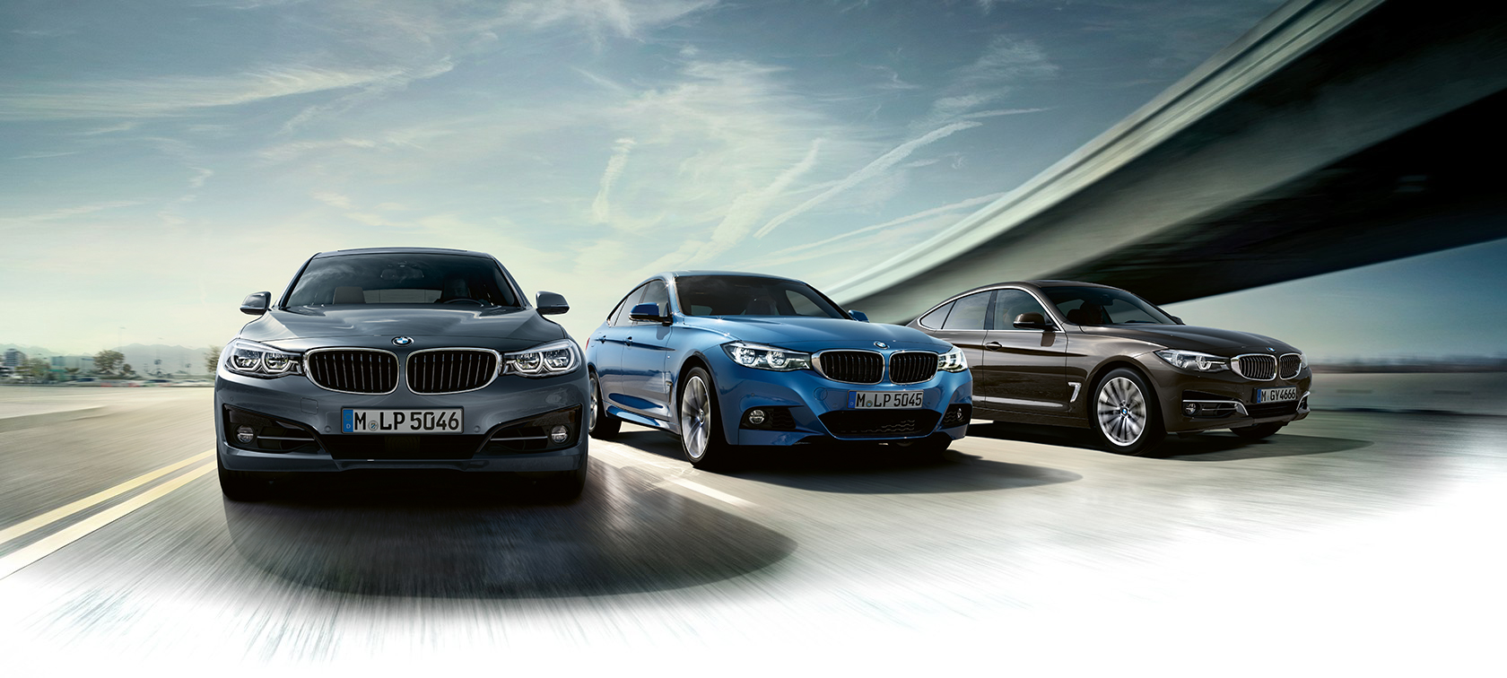 BMW 3 Series Gran Turismo in grey, blue and brown metallic colours on the racetrack.