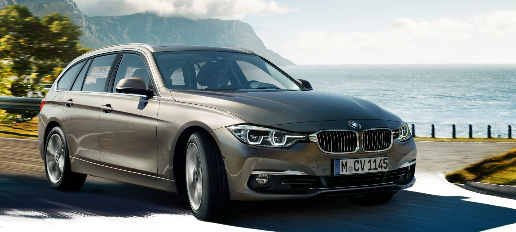 BMW 3 Series in brown metallic by mountains and lake.