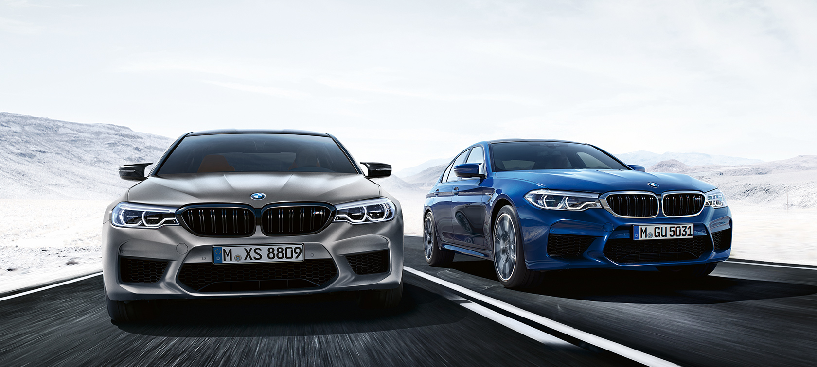 BMW M5 Sedan: grey and blue metallic cars are driving on highway in the snow.