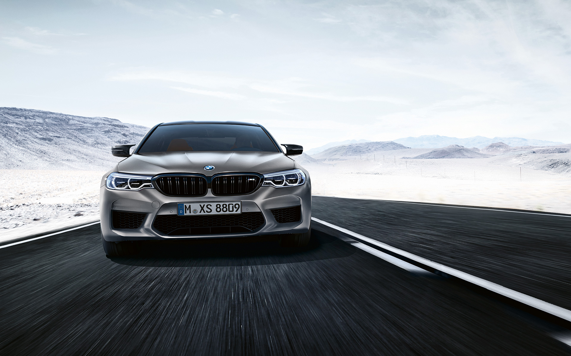 Grey M5 Competition in front view driving on highway in front of desert landscape