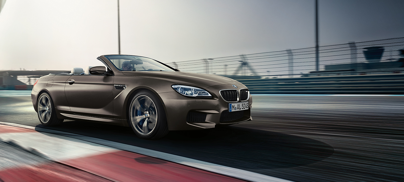 BMW M Series M6 Convertible in brown metallic driving on highway.