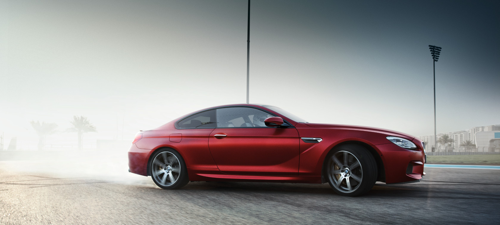 BMW M Series M6 Coupe in metallic red side view car drifting.