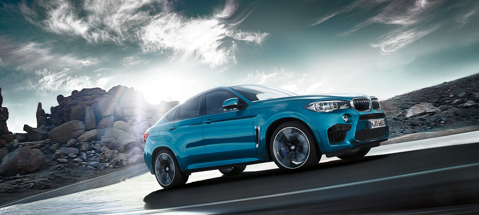 BMW M Series X6M: matallic blue car is driving up the mountain with sunlight.