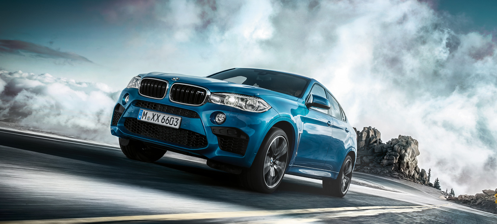 BMW X6M in metallic blue: frontside view uphill.