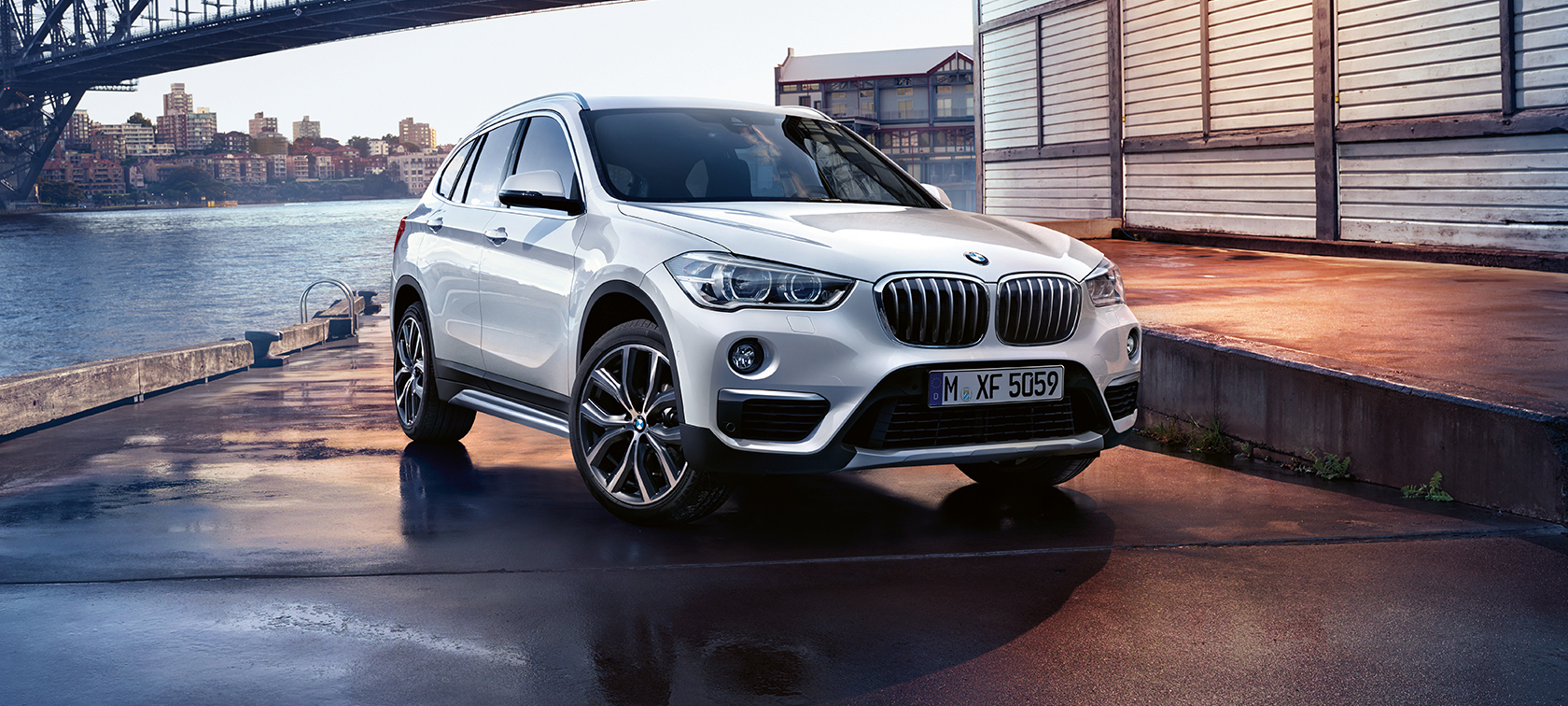 BMW X Series X1: white car, three-quarter view, parked under the bridge.