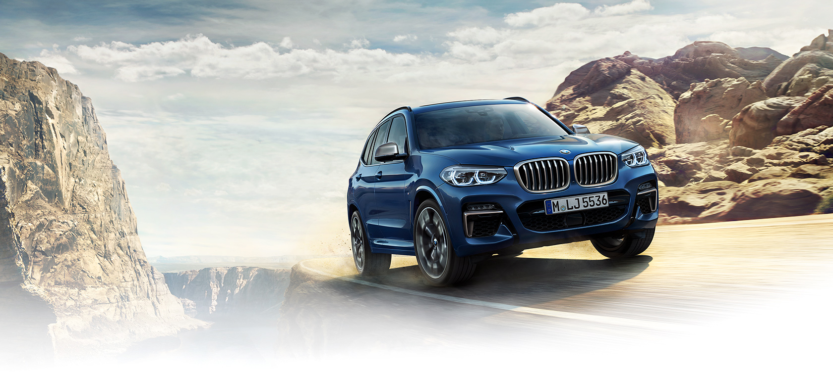 BMW X Series X3: bright blue risky turn on mountaintop.