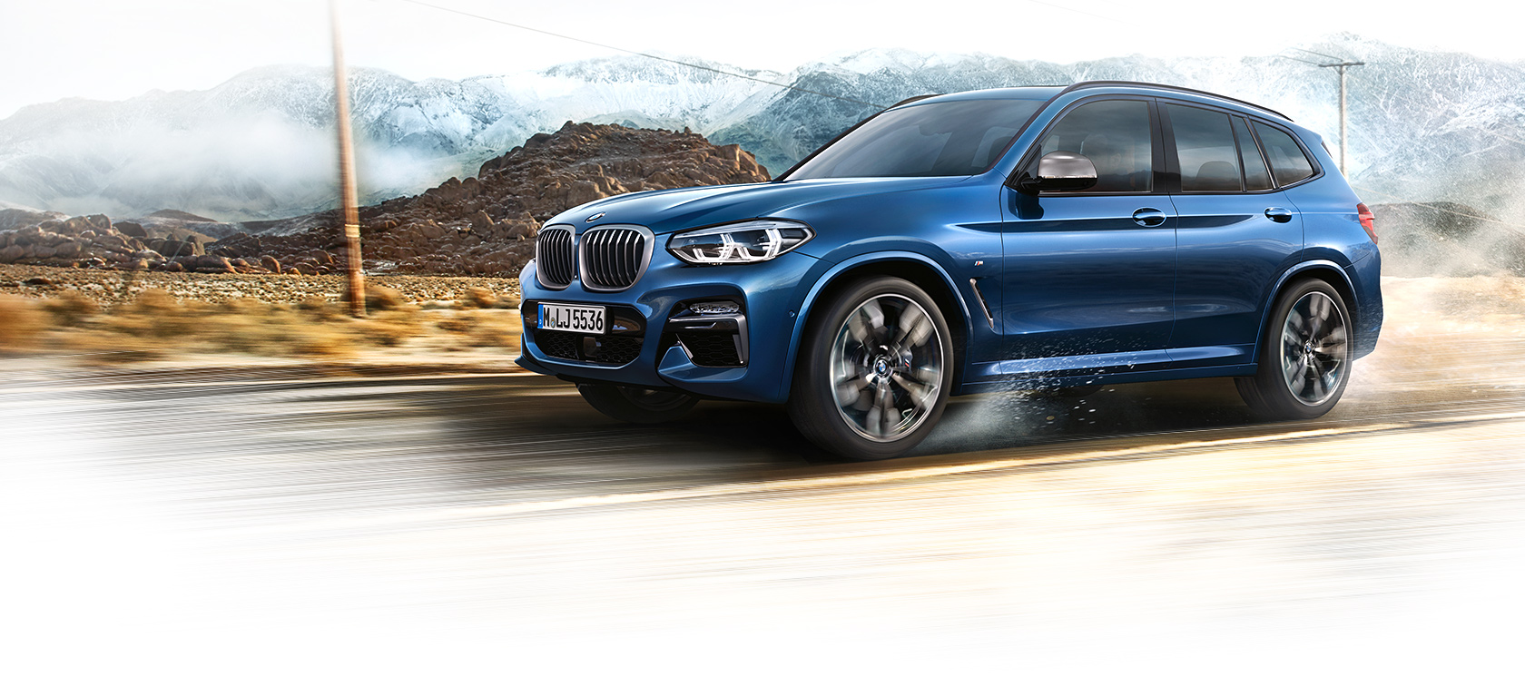 BMW X3 in metallic blue: three-quarter view of the car on the mountain road.
