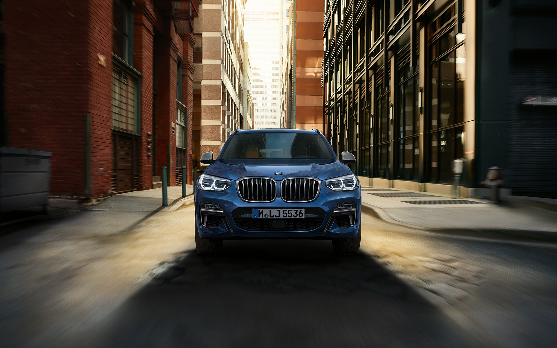 BMWX Series X3: front view of bright blue car between city buildings.