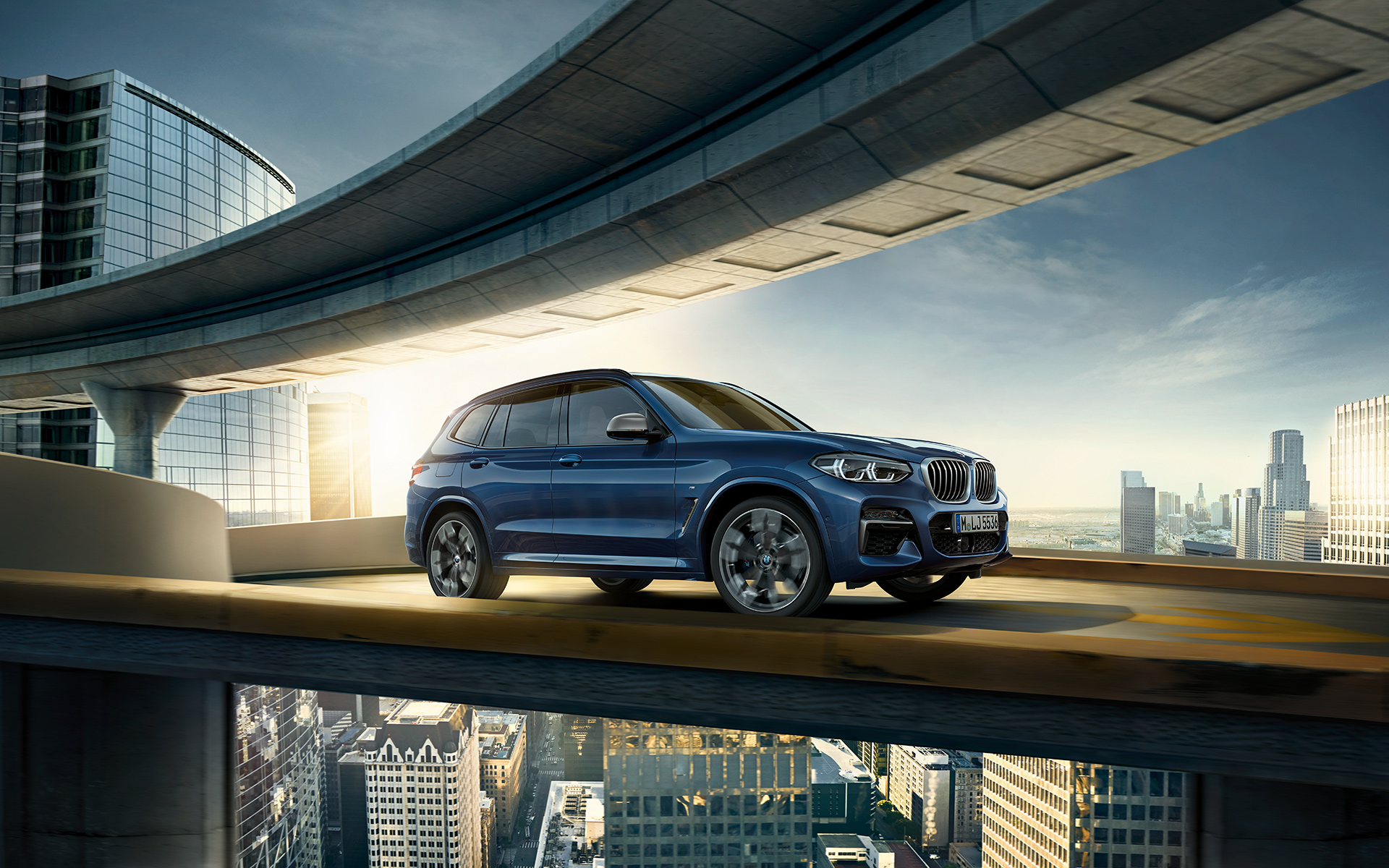 BMW X Series X3 high-performance metallic blue vehicle is driving on the futuristic city bridge.