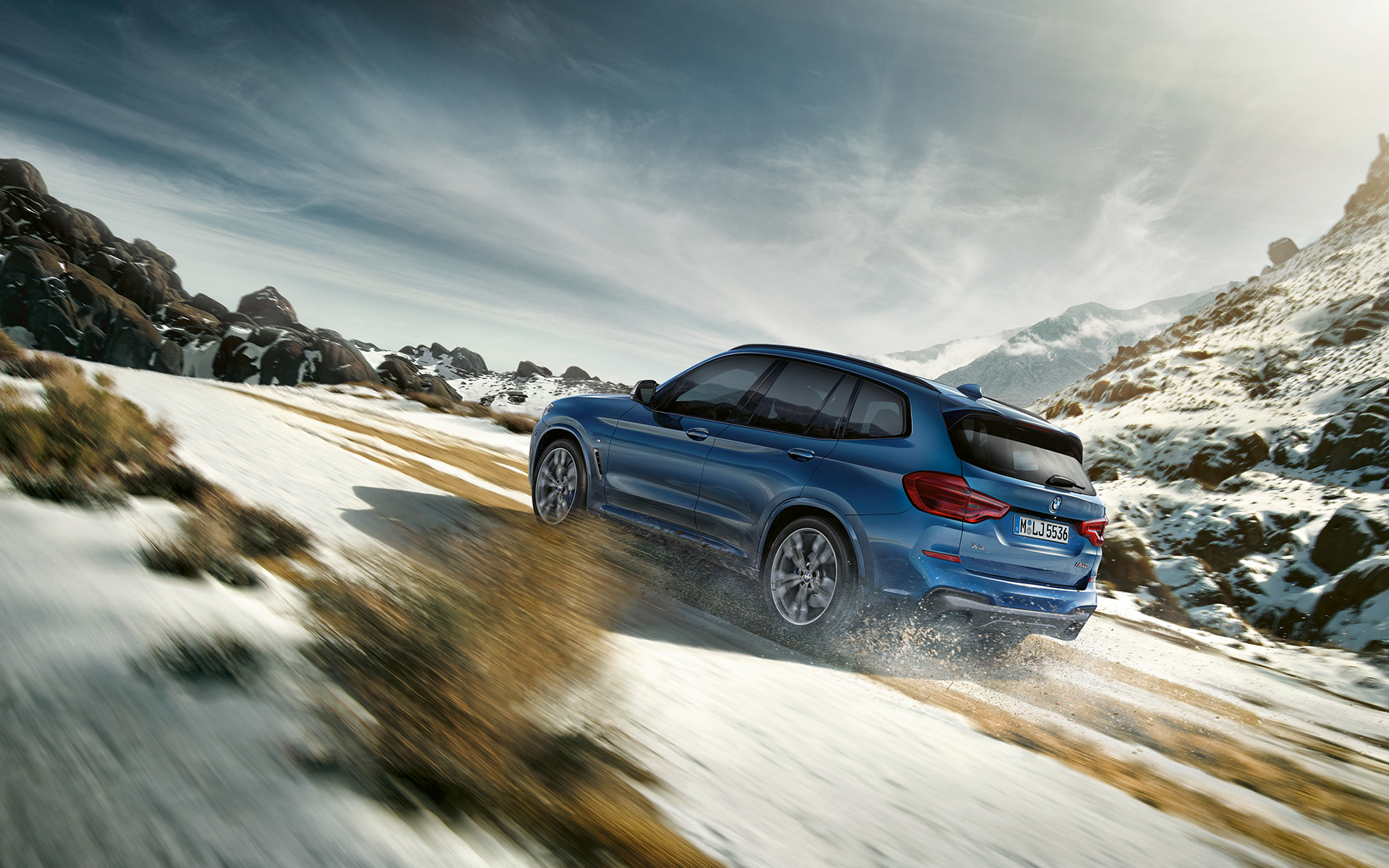 BMW X Series X3 in bright blue: fast drive off-road on the mountains.