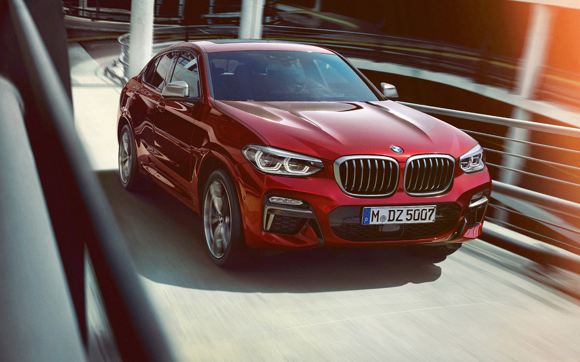 BMW X Series X4: metallic red front view driving up the highway.