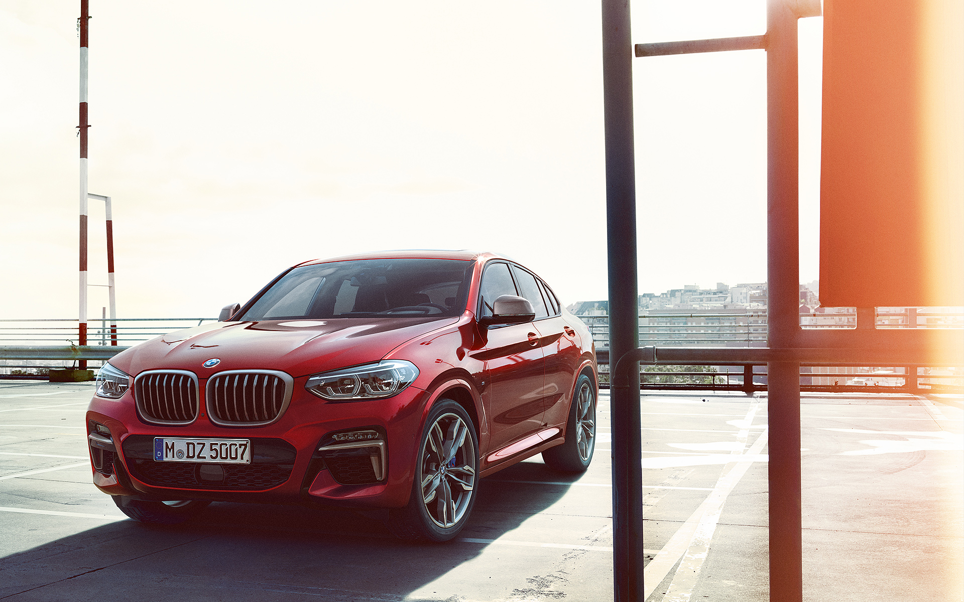 BMW X Series X4: metallic red vehicle in front view with city background.