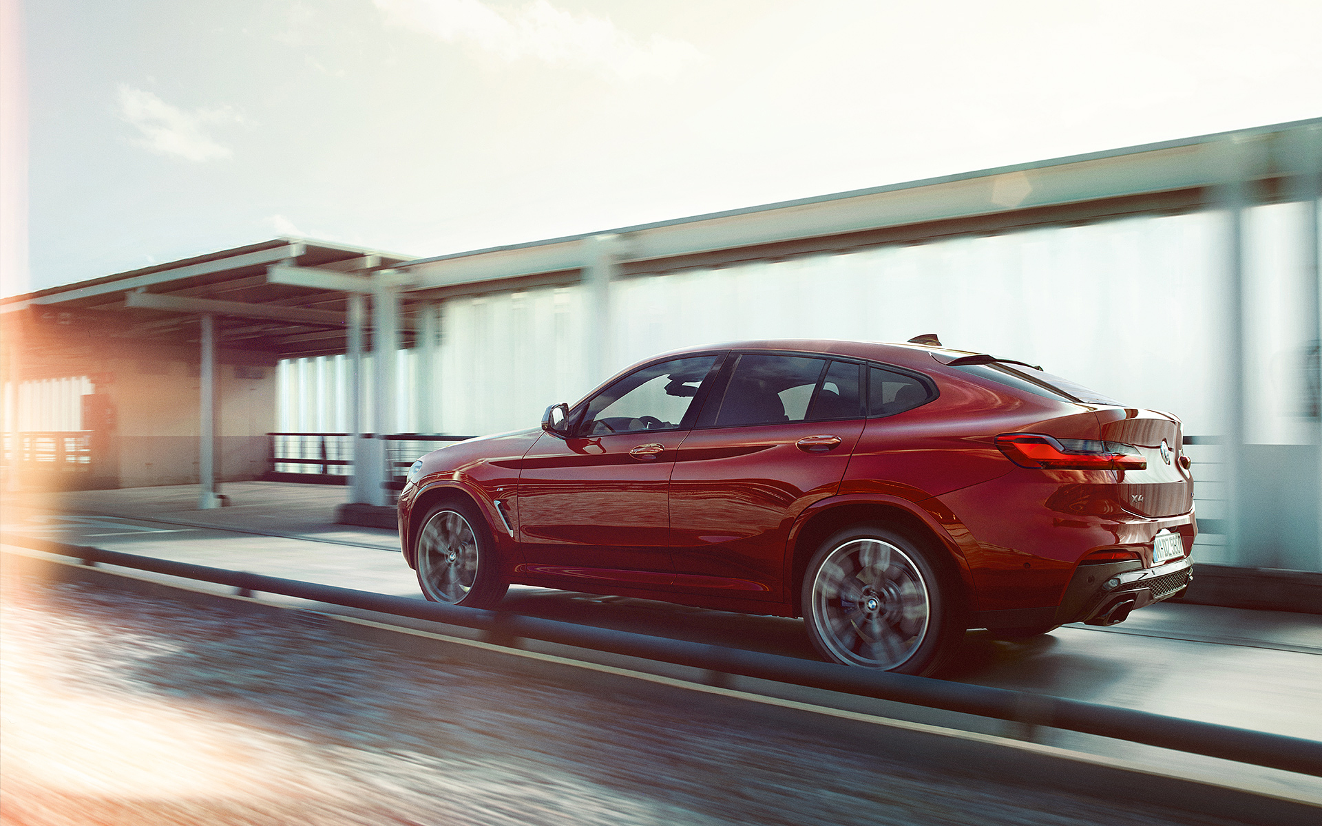 BMW X Series X4: metallic red three-quarter rear view, speedy car on the road.