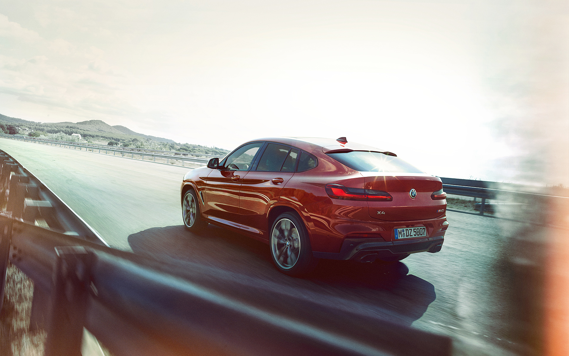 BMW X Series X4: red rear view highway driving in suburbs.