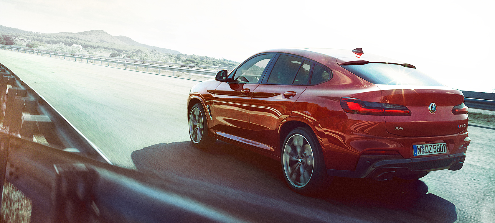 BMW X Series X4: metallic red vehicle on highway turn.