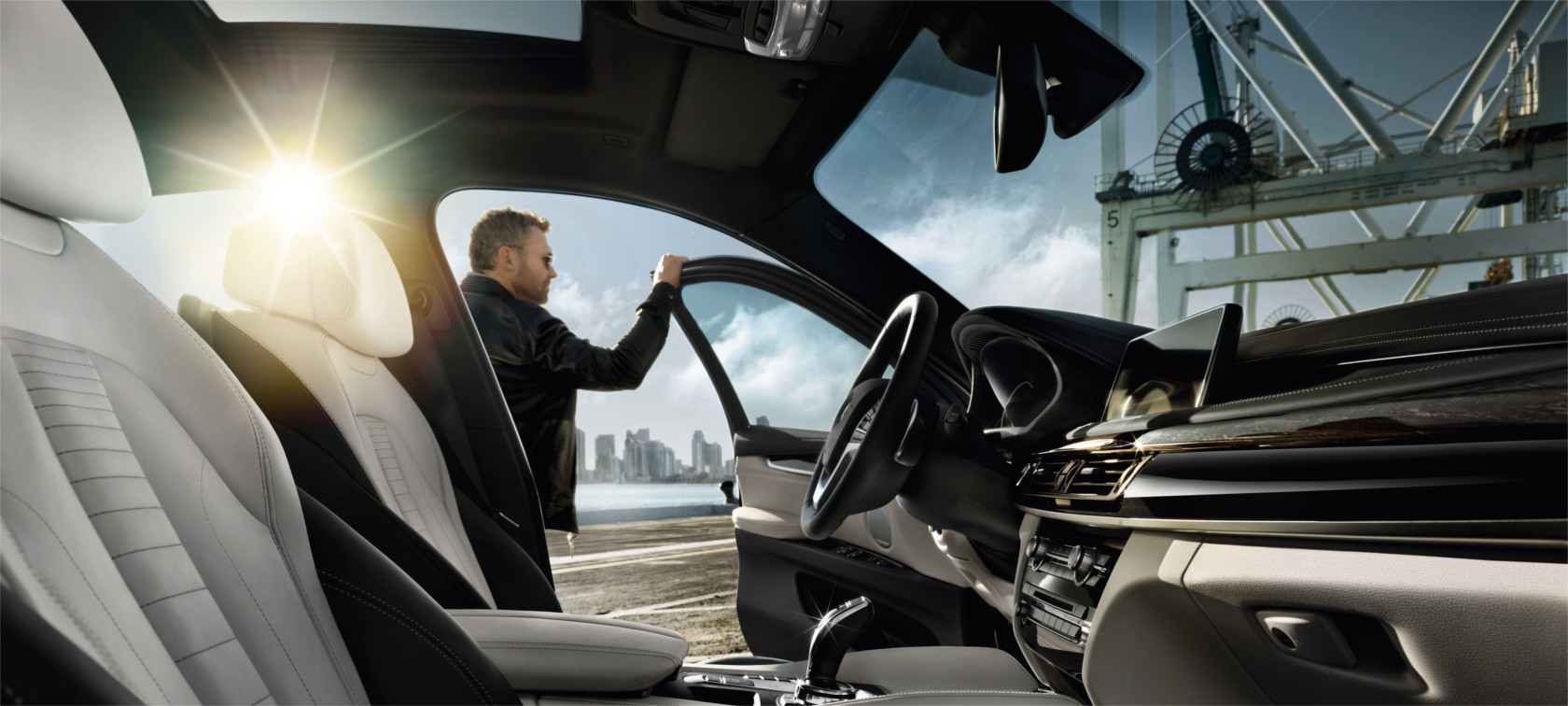 BMW X Series X6: black and white sports car interior with sunlight.