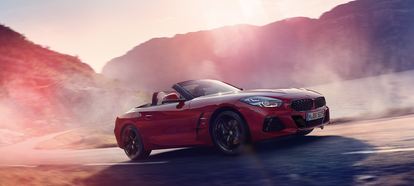 BMW Z Series Roadster: driving uphill in convertible red car.