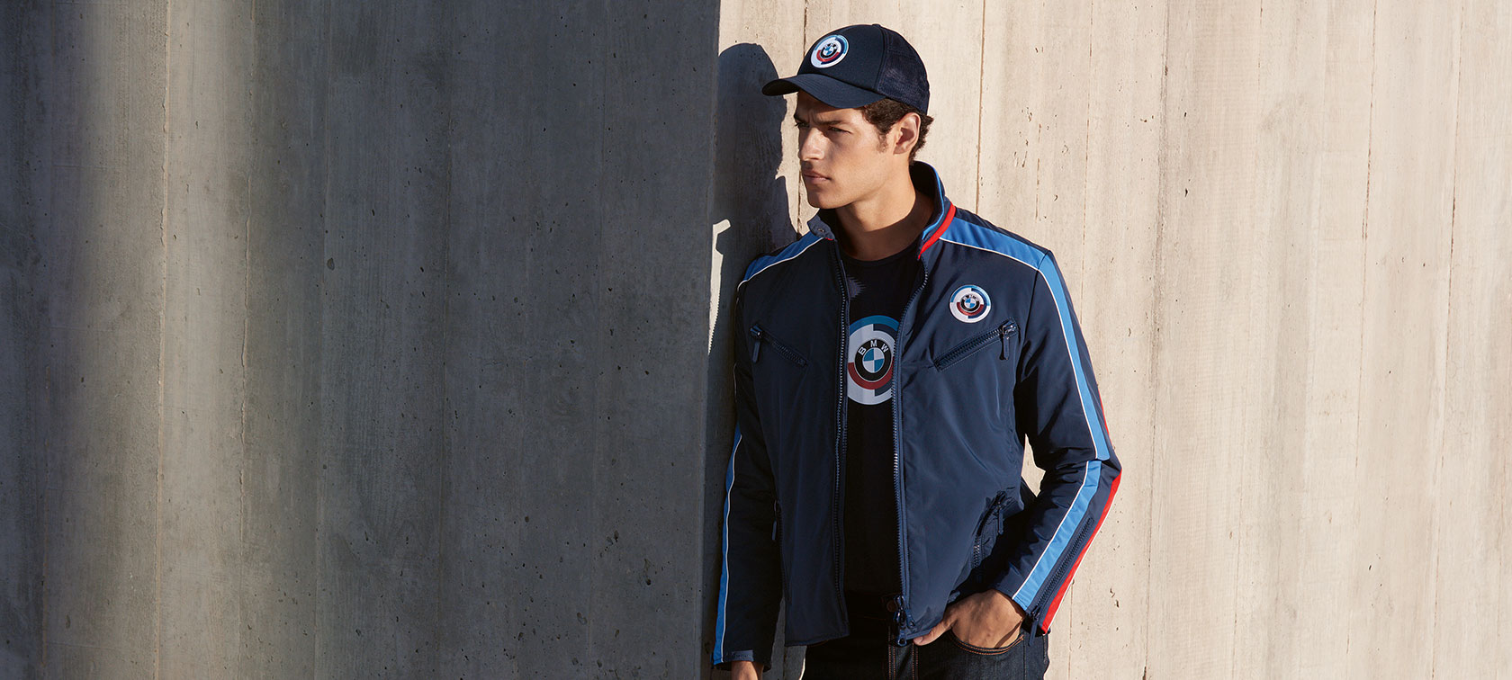 A man is shown wearing a BMW Classic Men's Motorsport Jacket from the BMW Classic Collection.