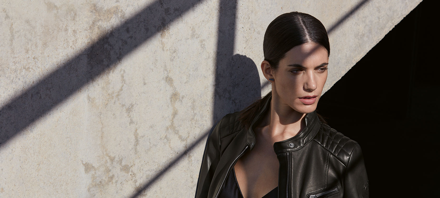 In the picture, a young woman is wearing the BMW Ladies Leather Jacket in front of an urban backdrop.