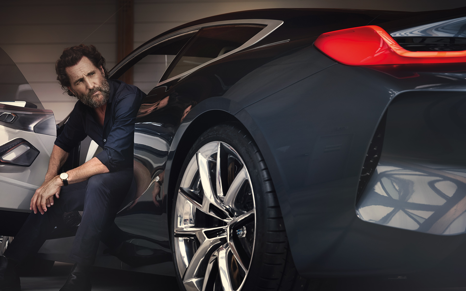 BMW 8 Series Coupe: elegant man sitting inside the black vehicle.