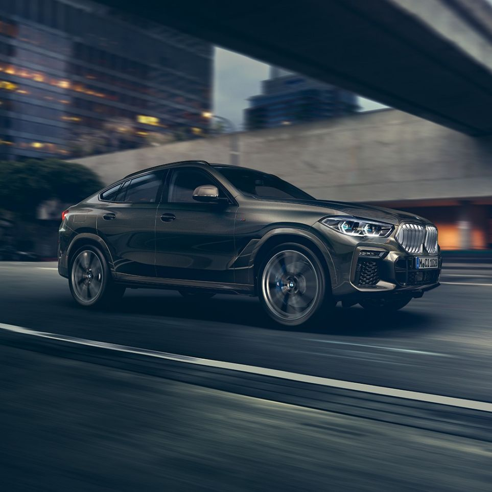 BMW X6 in three-quarter front perspective driving in front of an urban setting.